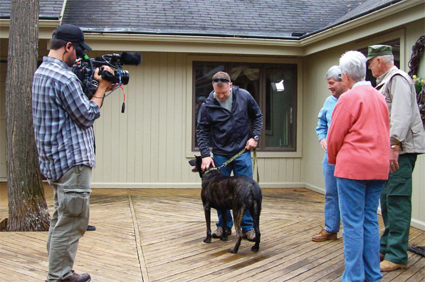 "Doug and Pam Davis along with ""Gunny"" look on as Remmy and Dan, his handler during the war in Afghanistan, greet each other during the filming of a future Sportsman Channel Documentary. Photo by: Priscilla Miller."