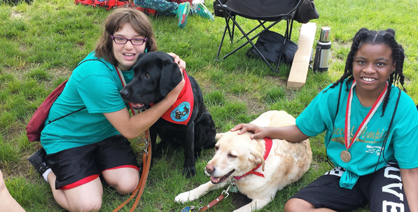 Lori Shaw's dogs, ALI AND ASIA with two children at the Special Olypics 2015. Ali is a 10-year-old yellow Lab and Asia is a six-year-old black Lab. Both are working therapy dogs who visit and work with children in schools, visit nursing homes and hospitals as well as many other events.