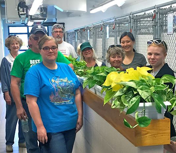 "Volunteers from Central United Methodist Church pose during the ""Plants for Pooches"" project in May. These beautiful additions to the dog kennel area add beauty and sound absorption. Many volunteers have contributed skills, time, material and energy into building ""The Wall."""
